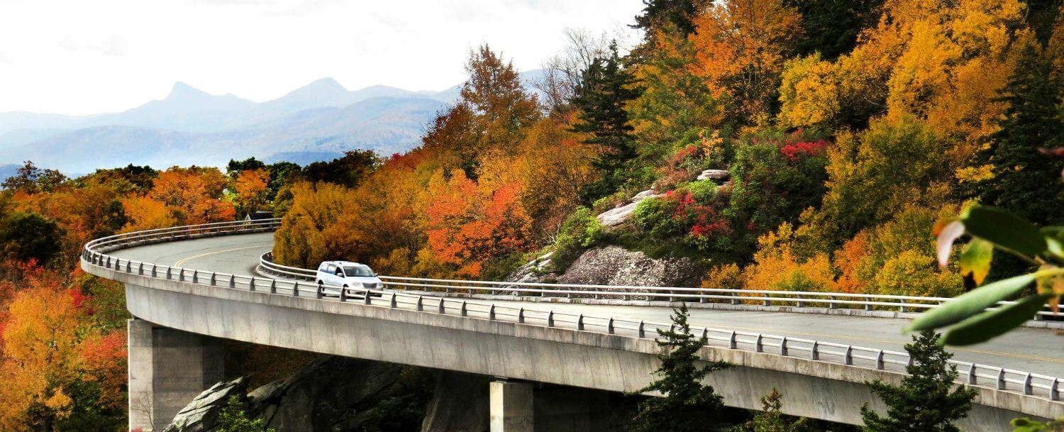 A car driving on the Blue Ridge Parkway pas a scenic mountain overlook.