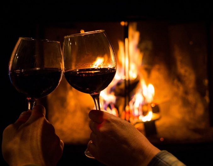 a couple holding two glasses of wine by the fireplace on a romantic getaway in NC.