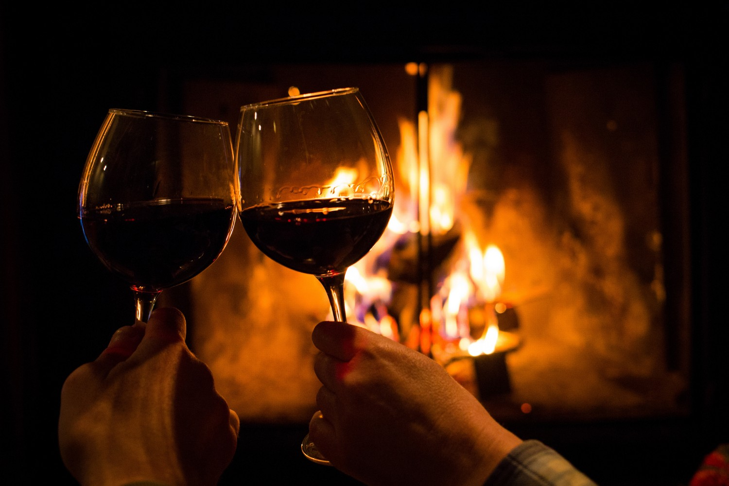 couple holding a pair of wine glasses by a fireplace