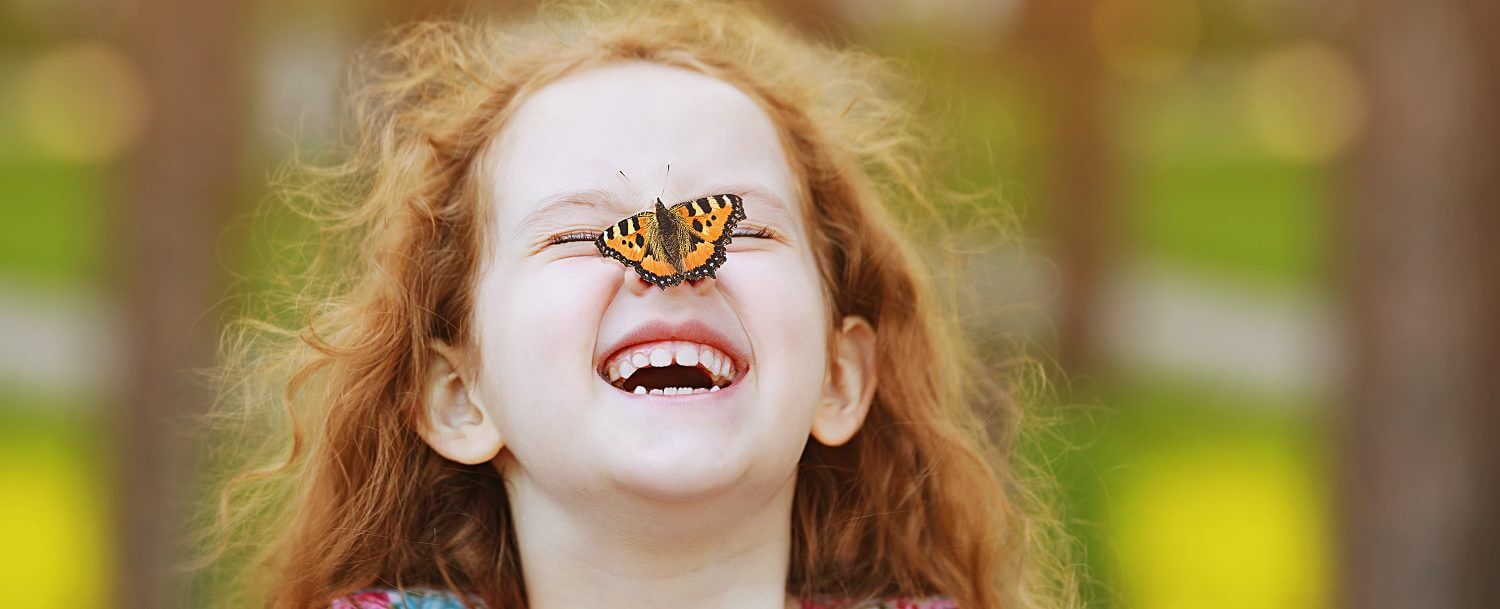 an-elementary-school-girl-with-a-butterfly-on-her-nose-visiting-the-lake-lure-flowering-bridge-one-of-the-best-things-to-do-in-asheville-with-kids-