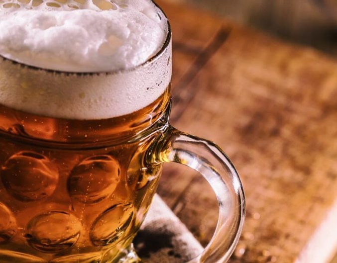 a-picture-of-a-cold-beer-with-a-frothy-head-inside-of-a-cold-mug-sitting-atop-a-wooden-board-and-napkin.-